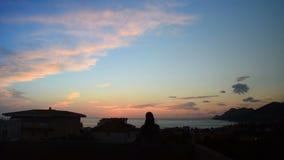 Jovem mulher que aprecia o crepúsculo sobre o mar do balcão vídeos de arquivo