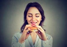 Jovem mulher que aprecia o fast food imagem de stock