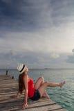 Jovem mulher que aprecia o por do sol no mar Fotografia de Stock Royalty Free