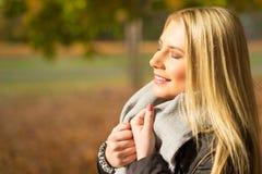 Jovem mulher que aprecia o sol do outono Imagem de Stock Royalty Free
