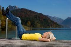 Jovem mulher que aprecia um dia de relaxamento no lago Fotografia de Stock