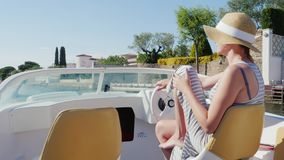 Jovem mulher que aprecia um feriado no recurso europeu Flutuando em um barco no canal Empuriabrava, Espanha filme