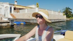 Jovem mulher que aprecia um recurso de feriado em Europa Flutuando em um barco no canal Empuriabrava, Espanha video estoque