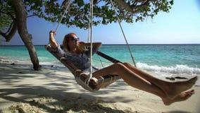 Jovem mulher que aprecia um resto em uma rede na praia tropical filme