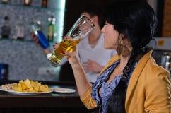 Jovem mulher que aprecia uma cerveja na barra imagem de stock