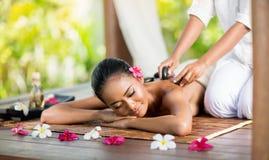 Jovem mulher que aprecia uma massagem de pedra quente Fotos de Stock