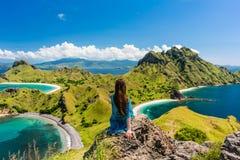 Jovem mulher que aprecia a vista impressionante da ilha de Padar durante a soma Fotos de Stock