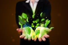 A jovem mulher que apresenta a eco a folha verde recicla o conceito da energia foto de stock