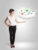 Jovem mulher que apresenta a nuvem com ícones coloridos e símbolos do app Imagem de Stock