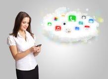Jovem mulher que apresenta a nuvem com ícones coloridos e símbolos do app Foto de Stock
