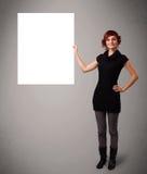 Jovem mulher que apresenta o espaço branco da cópia em papel Foto de Stock