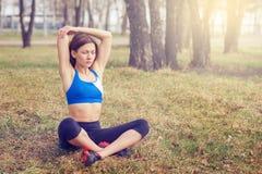 Jovem mulher que aquece-se antes de uma corrida Uma maneira de vida saudável Aptidão dos esportes Fotografia de Stock