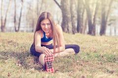 Jovem mulher que aquece-se antes de uma corrida Uma maneira de vida saudável Aptidão dos esportes Imagem de Stock