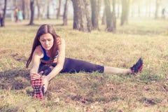 Jovem mulher que aquece-se antes de uma corrida Uma maneira de vida saudável Aptidão dos esportes Fotografia de Stock Royalty Free