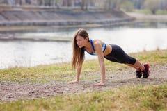 Jovem mulher que aquece-se antes de uma corrida Uma maneira de vida saudável Aptidão dos esportes Imagens de Stock