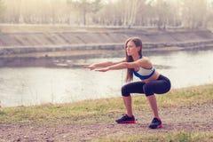 Jovem mulher que aquece-se antes de uma corrida Uma maneira de vida saudável Aptidão dos esportes Fotos de Stock