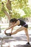 Jovem mulher que aquece-se com estiramentos no banco de parque Fotografia de Stock Royalty Free