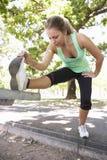 Jovem mulher que aquece-se com estiramentos no banco de parque Fotos de Stock