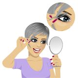 Jovem mulher que arranca suas sobrancelhas com a pinça que olha o espelho Imagem de Stock