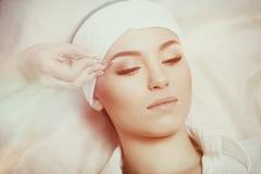 Jovem mulher que arranca suas sobrancelhas no bar da beleza fotos de stock royalty free