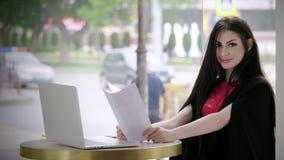 Jovem mulher que assina o contrato importante e sorrisos agradáveis em um bar da tabela no fundo do tráfego urbano video estoque