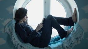 Jovem mulher que atravessa um livro de leitura A moça bonita no pijama senta-se em uma janela redonda que lê um livro filme