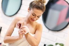 Jovem mulher que barbeia as axila no banheiro imagens de stock