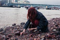 Jovem mulher que beachcombing na cidade Fotografia de Stock Royalty Free