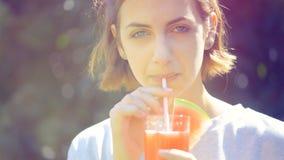 Jovem mulher que bebe o suco fresco da melancia video estoque