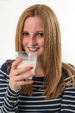 Jovem mulher que bebe um vidro do leite fotografia de stock