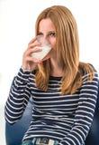 Jovem mulher que bebe um vidro do leite fotografia de stock royalty free
