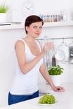 Jovem mulher que bebe uma garrafa da água em sua cozinha fotografia de stock
