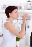 Jovem mulher que bebe uma garrafa da água em sua cozinha imagens de stock royalty free