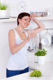 Jovem mulher que bebe uma garrafa da água em sua cozinha imagens de stock