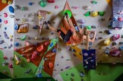 Jovem mulher que bouldering na parede pendendo sobre no gym de escalada fotos de stock