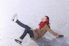 Jovem mulher que cai quando patinagem no gelo Fotografia de Stock Royalty Free