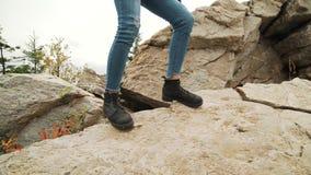 Jovem mulher que caminha acima as botas de couro vestindo do alpinismo da inclinação de montanha Menina do caminhante no passeio  vídeos de arquivo