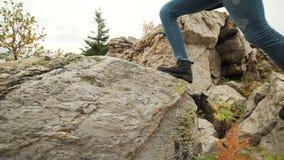 Jovem mulher que caminha acima as botas de couro vestindo do alpinismo da inclinação de montanha Menina do caminhante no passeio  filme