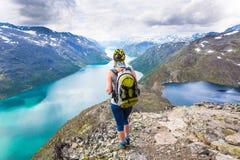 Jovem mulher que caminha em Besseggen A menina feliz aprecia o lago bonito e o bom tempo em Noruega Imagens de Stock