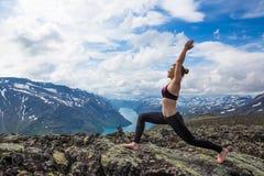 Jovem mulher que caminha em Besseggen A menina feliz aprecia o lago bonito e o bom tempo em Noruega Foto de Stock