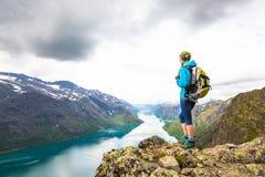 Jovem mulher que caminha em Besseggen A menina feliz aprecia o lago bonito e o bom tempo em Noruega Imagem de Stock