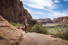 A jovem mulher que caminha na garganta vermelha bonita da rocha com um cênico negligencia Imagem de Stock