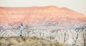 Jovem mulher que caminha nas montanhas entre rochas naturais de Cappadocia imagem de stock royalty free