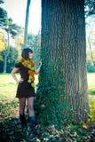 Jovem mulher que caminha no parque do outono vestido no vestido feito malha Fotografia de Stock Royalty Free