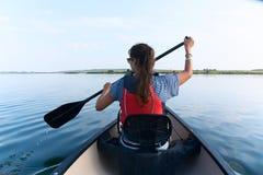 Jovem mulher que canoeing no lago em um dia de verão Fotografia de Stock
