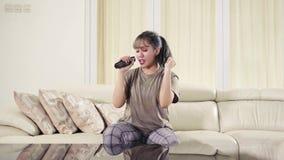 Jovem mulher que canta com controlo a distância video estoque