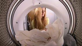 Jovem mulher que carrega o a roupa à máquina de lavar filme