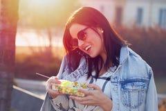 Jovem mulher que chama com salada nas mãos foto de stock