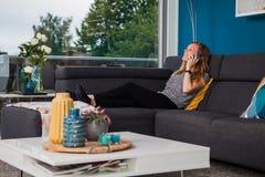 Jovem mulher que chama e que ri alto no sofá imagens de stock