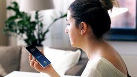 Jovem mulher que chama o smartphone em casa filme